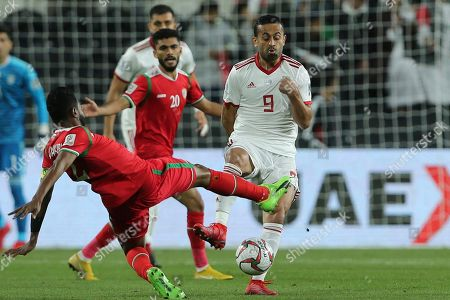 Oman's defender Mohammas Al-Musala, left, tries to blocks Iran's midfielder Omid Ebrahimi, right, during the AFC Asian Cup round of 16 soccer match between Iran and Oman at Mohammed Bin Zayed Stadium in Abu Dhabi, United Arab Emirates