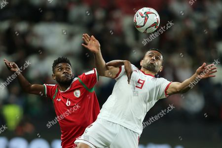 Oman's midfielder Raed Saleh, left, and Iran's midfielder Omid Ebrahimi jump for the ball during the AFC Asian Cup round of 16 soccer match between Iran and Oman at Mohammed Bin Zayed Stadium in Abu Dhabi, United Arab Emirates