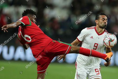 Oman's midfielder Raed Saleh, left, fights for the ball with Iran's midfielder Omid Ebrahimi during the AFC Asian Cup round of 16 soccer match between Iran and Oman at Mohammed Bin Zayed Stadium in Abu Dhabi, United Arab Emirates