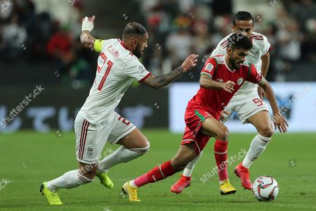 Oman's midfielder Salaah Al-Yahyaei, center, runs with ball against Iran's midfielder Ashkan Dejagah, left, and Iran's midfielder Omid Ebrahimi during the AFC Asian Cup round of 16 soccer match between Iran and Oman at Mohammed Bin Zayed Stadium in Abu Dhabi, United Arab Emirates