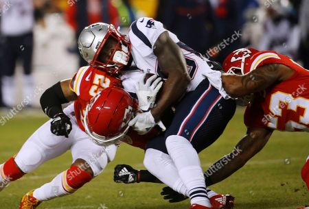 New England Patriots running back Sony Michel (26) is tackled by Kansas City Chiefs defensive back Eric Berry (29) and inside linebacker Anthony Hitchens (53) during the first half of the AFC Championship NFL football game, in Kansas City, Mo
