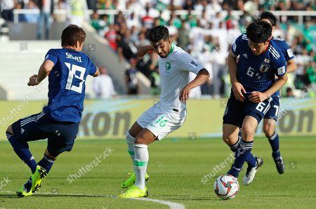 Saudi Arabia's midfielder Hussain Al-Mogahwi, center, is closed down by Japan's defender Hiroki Sakai, left, and Wataru Endo during the AFC Asian Cup round of 16 soccer match between Japan and Saudi Arabia at the Sharjah Stadium in Sharjah, United Arab Emirates