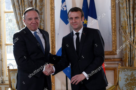 French President Emmanuel Macron greets Quebec Premier Francois Legault, left, prior to their meeting at the Elysee Palace in Paris, France
