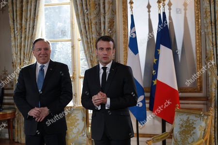 French President Emmanuel Macron speaks to the media as he greets Quebec Premier Francois Legault, left, prior to their meeting at the Elysee Palace in Paris, France