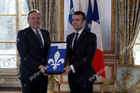 French President Emmanuel Macron poses with Quebec Premier Francois Legault, left, after receiving a gift prior to their meeting at the Elysee Palace in Paris, France