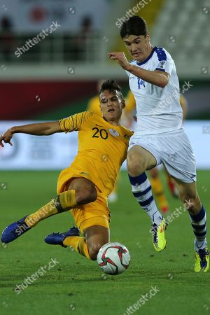 Australia's defender Trent Sainsbury, left, fights for the ball with Uzbekistan's forward Eldor Shomurodov during the AFC Asian Cup round of 16 soccer match between Australia and Uzbekistan at the Khalifa bin Zayed Stadium in Al Ain, United Arab Emirates