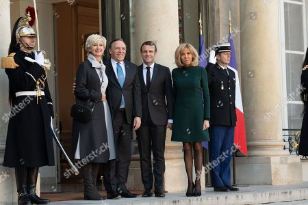 French President Emmanuel Macron and his wife Brigitte Trogneux welcome Quebec Prime Minister Francois Legault and his wife Isabelle Brais as they arrive for a meeting at the Elysee Palace