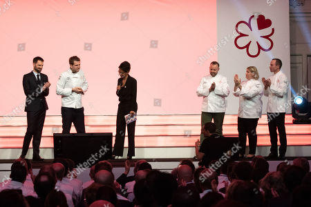 Gwendal Poullennec (L), the new international director of the Guide Michelin, applauds French chef Alexandre Mazzia (2-L), standing next to  journalist Audrey Pulvar (3-L) and watched by French chefs David Toutain (3-R), Stephanie Le Quellec (2-R) and Christophe Hay (R) who all received a second star during the 2019 Michelin Guide presentation in Paris, France, 21 January 2019. The Michelin Guide is a series of guide books published by the French tyre company Michelin and is a reference guide to European hotels and restaurants with select establishments receiving stars for excellence.