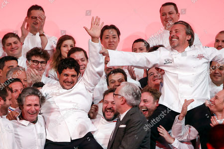 French Chef Laurent Petit, right, from the Clos des Sens restaurant in Annecy, French Alps, and Argentine Chef Mauro Colagreco, left, from the Mirazur restaurant in Menton, French Riviera, celebrate on stage with other chefs after being awarded with Three Michelin Star during the 2019 Michelin Guide ceremony, in Paris, France, . French Chef Alain Ducasse standing in the middle front row looks on