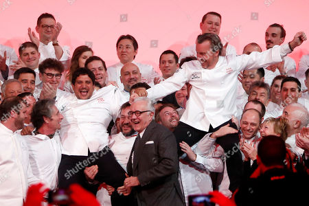 French Chef Laurent Petit, right, from the Clos des Sens restaurant in Annecy, French Alps, and Argentine Chef Mauro Colagreco, left, from the Mirazur restaurant in Menton, French Riviera, celebrate on stage with other chef after being awarded with Three Michelin Star during the 2019 Michelin Guide ceremony, in Paris, France, . French Chef Alain Ducasse stands in the middle front row
