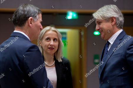 Slovenian Finance Minister Andrej Bertoncelj, left, speaks with Polish Minister of Finance Teresa Czerwinska, center, and Romanian Finance Minister Eugene Teodorovici during a meeting of EU finance ministers at the Europa building in Brussels