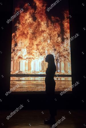 A gallery employee poses next to a video art installation by US artist Bill Viola, entitled 'Tristan's Ascension (The Sound of a Mountain Under a Waterfall),' during the press day for the exhibition 'Bill Viola / Michelangelo: Life and Rebirth' at the Royal Academy of Arts in London, Britain, 22 January 2019. The exhibit will open to the public from 26 January to 31 March 2019.