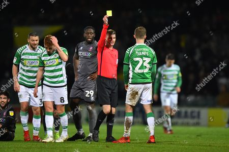 Referee Ollie Yates show a yellow card to Tom James (23) of Yeovil Town after he fouled Tom Pett (7) of Lincoln City during the EFL Sky Bet League 2 match between Yeovil Town and Lincoln City at Huish Park, Yeovil