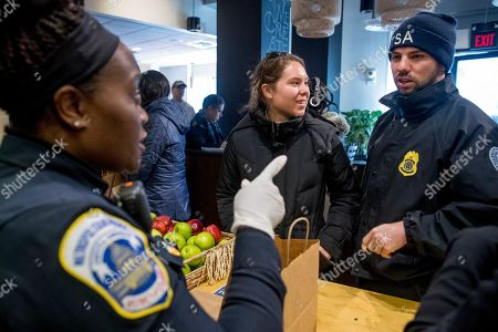 Shane Smith, Adriane Benson. Metropolitan Police Officer and volunteer Adriane Benson, left, takes a food order for Shane Smith, a TSA agent, right, as he and other furloughed government workers affected by the shutdown receive free food and supplies at World Central Kitchen, the not-for-profit organization started by Chef Jose Andres, in Washington. The organization devoted to providing meals in the wake of natural disasters, has set up a distribution center just blocks from the U.S. Capitol building to assist those affected by the government shutdown