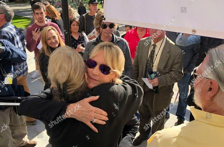 Stock Photo of Consumer advocate Erin Brockovich, who famously took on Pacific Gas & Electric Co. in the 1990s, hugs Franchine Ehler after standing with wildfire victims and speaking outside the state Capitol, in Sacramento, Calif. Brockovich is urging California lawmakers not to let PG&E go bankrupt because it might mean less money for wildfire victims