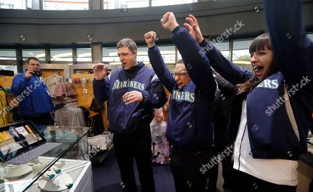Stock Image of Former Seattle Mariners catcher Dan Wilson, left, celebrates with Mariners' marketing department workers Gregg Greene, center, and Camden Finney as they watch an announcement that Edgar Martinez will be inducted into baseball's Hall of Fame, in Seattle. Martinez, a former teammate of Wilson, was the long-time Mariners' designated hitter