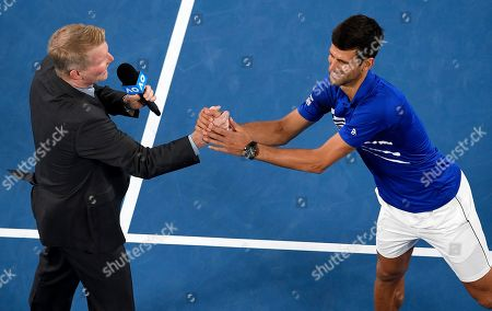 Serbia's Novak Djokovic right, shakes hands with Jim Courier following an on court interview after Japan's Kei Nishikori retired injured from their quarterfinal match at the Australian Open tennis championships in Melbourne, Australia