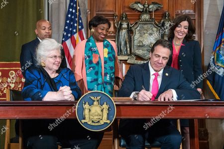 In this photo provided by the Office of Gov. Andrew M. Cuomo, Cuomo, right, signs Reproductive Health Act Legislation during a ceremony, in the Red Room at the State Capitol in Albany, N.Y. With the new law, New York state enacts one of the nation's strongest protections for abortion rights, a move that state leaders say was needed to safeguard those rights should the U.S. Supreme Court overturn Roe v. Wade