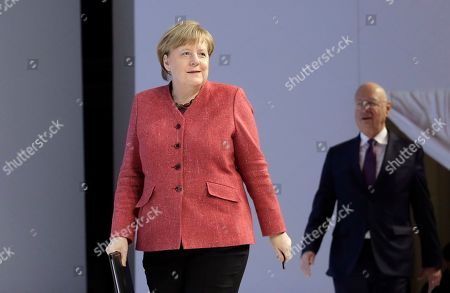 German Chancellor Angela Merkel enters the stage followed by Klaus Schwab, founder and Executive Chairman of the World Economic Forum, at the annual meeting of the World Economic Forum in Davos, Switzerland