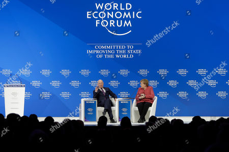 Klaus Schwab, founder and Executive Chairman of the World Economic Forum, talks with German Chancellor Angela Merkel after she addressed the annual meeting of the World Economic Forum in Davos, Switzerland