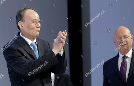 Chinese Vice President Wang Qisan applauds as he enters the stage with Klaus Schwab, founder and Executive Chairman of the World Economic Forum, at the annual meeting of the World Economic Forum in Davos, Switzerland