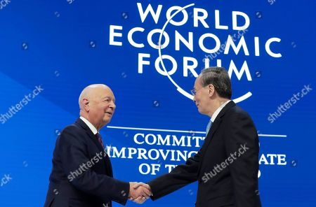 Chinese Vice President Wang Qisan, right, shakes hands with Klaus Schwab, founder and Executive Chairman of the World Economic Forum, before addressing the annual meeting of the World Economic Forum in Davos, Switzerland