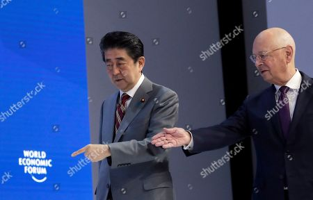 Japanese Prime Minister Shinzo Abe, left, and Klaus Schwab, founder and Executive Chairman of the World Economic Forum, enter the stage at the annual meeting of the World Economic Forum in Davos, Switzerland