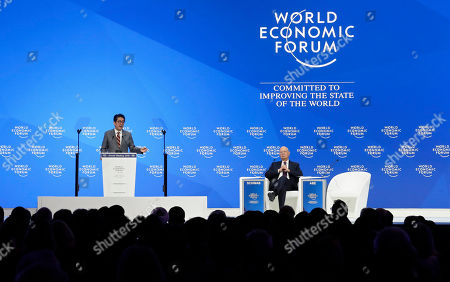 Klaus Schwab, founder and Executive Chairman of the World Economic Forum, listens as Japanese Prime Minister Shinzo Abe, left, addresses the annual meeting of the World Economic Forum in Davos, Switzerland
