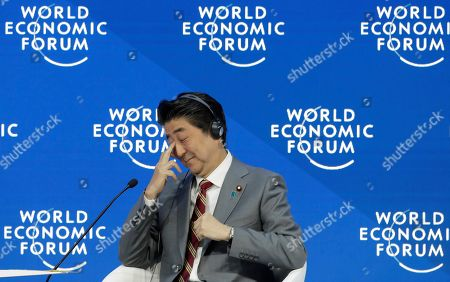 Japanese Prime Minister Shinzo Abe listens to Klaus Schwab, founder and Executive Chairman of the World Economic Forum, after addressing the annual meeting of the World Economic Forum in Davos, Switzerland
