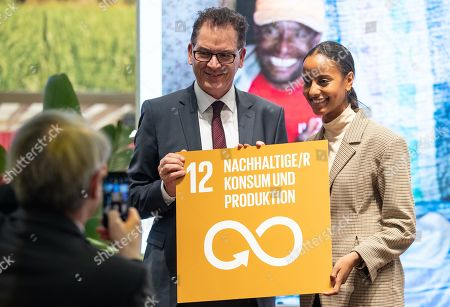 Germany's Minister for Economic Cooperation and Development Gerd Mueller (C) and the Ambassador of Fair Trade of the German Federal Ministry of Economic Cooperation and Development (German: Bundesministerium für wirtschaftliche Zusammenarbeit und Entwicklung, BMZ), model Sara Nuru (R) pose with a placard reading: 'Sustainable Consumption and Production' at the International Green Week fair in Berlin, Germany, 23 January 2019. The International Green Week fair runs from 18 to 27 January 2019. This year's partner country is Finland.
