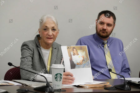 Liz White displays a photo of herself holding, Matt White, right, after giving birth during a news conference before a committee hearing at the Statehouse, Indianapolis