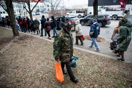 Furloughed federal worker James Grant carries food distributed by Philabundance volunteers as others affected by the partial government shutdown wait in line to receive their parcels in Philadelphia