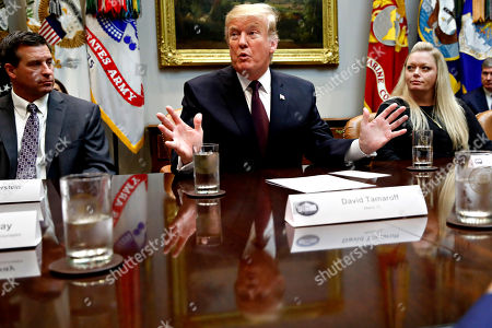 President Donald Trump is reflected in the table as he gestures while speaking during a healthcare roundtable in the Roosevelt Room of the White House, in Washington. With the president are David Silverstein, of Denver, left, and Jamesia Shutt, of Aurora, Colo., right