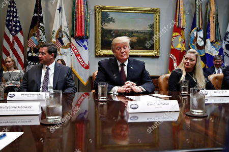 President Donald Trump listens during a healthcare roundtable in the Roosevelt Room of the White House, in Washington. With the president are David Silverstein, of Denver, left, and Jamesia Shutt, of Aurora, Colo., right
