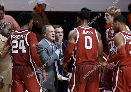 Oklahoma coach Lon Kruger talks with his team during a timeout in the second half of an NCAA college basketball game against Oklahoma State in Stillwater, Okla