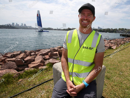 Australian skipper Tom Slingsby sits on the edge of Sydney Harbour as the French boat floats behind him as preparations for the SailGP series are underway in Sydney. The new sailing league founded by tech billionaire Larry Ellison and five-time America's Cup winner Russell Coutts will leap from concept to reality next month when six souped-up catamarans hit the starting line off Shark Island in Sydney Harbor