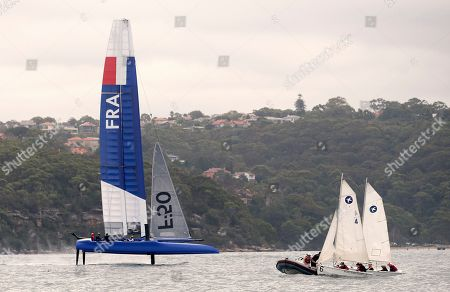 The French boat, left, sails past 2 smaller sailboats as it is tested on Sydney Harbor by a crew of members from several different teams as preparations for the SailGP series are underway in Sydney, . The new sailing league founded by tech billionaire Larry Ellison and five-time America's Cup winner Russell Coutts will leap from concept to reality next month when six souped-up catamarans hit the starting line off Shark Island in Sydney Harbor
