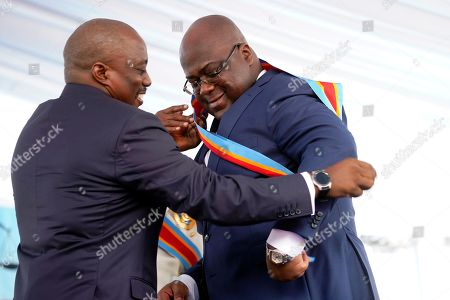 Congolese President Felix Tshisekedi, right, receives the presidential sash from outgoing president Joseph Kabila after being sworn in in Kinshasa, Democratic Republic of the Congo,. Tshisekedi won an election that raised numerous concerns about voting irregularities amongst observers as the country chose a successor to longtime President Kabila