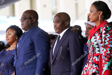Congolese President Felix Tshisekedi, second left, his wife Denise Nyekeru, outgoing president Jospeh Kabila and his wife Olive Lembe di Sita, listen to the national anthem during the inauguration ceremony, in Kinshasa. Tshisekedi won an election that raised numerous concerns about voting irregularities amongst observers as the country chose a successor to longtime President Joseph Kabila