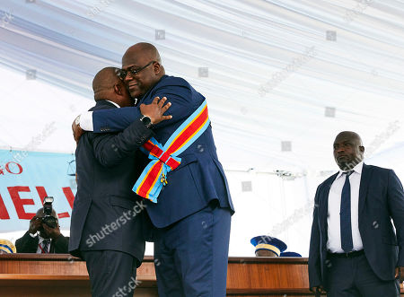 DR Congo's new President Felix Tshisekedi (C) and the outgoing President Joseph Kabila (L) embrace each other during the inauguration ceremony at the Palais de Nation in Kinshasa, the Democratic Republic of the Congo, 24 January 2019. Tshisekedi, the son of the country's veteran opposition leader, was sworn-in as the country's new President after disputed elections.