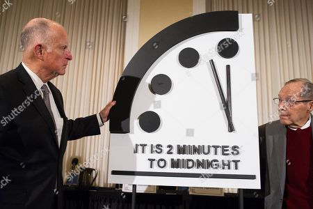 Former California Gov. Jerry Brown, left, and former Secretary of Defense William Perry unveil the Doomsday Clock during The Bulletin of the Atomic Scientists news conference in Washington, . The Doomsday Clock is set at two minutes to Midnight