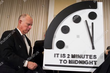Former California Gov. Jerry Brown unveils the Doomsday Clock during The Bulletin of the Atomic Scientists news conference in Washington, . The Doomsday Clock is set at two minutes to Midnight