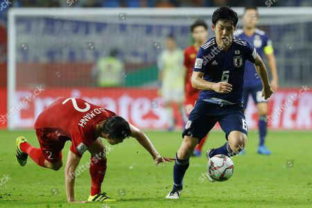 Japan's defender Wataru Endo, right, fights for the ball with Vietnam's defender Do Duy Manh during the AFC Asian Cup quarterfinal soccer match between Japan and Vietnam at Al Maktoum Stadium in Dubai, United Arab Emirates