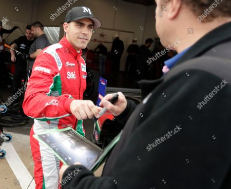 Pastor Maldonado, of Venezuela, left, signs autographs for fans after a practice session for the IMSA 24 hour race at Daytona International Speedway, in Daytona Beach, Fla