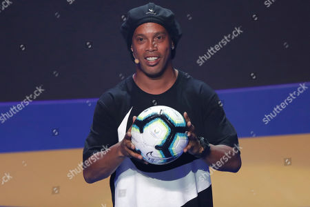 Brazil's Ronaldinho Gaucho shows the official ball during the draw for the 2019 Copa America soccer tournament in Rio de Janeiro, Brazil, . Brazil will host the continental soccer tournament in June and July