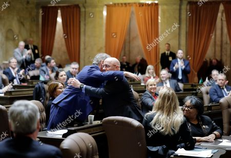 Rep. Roger Goodman, left, D-Kirkland and chair of the House Public Safety Committee, hugs Rep. Brad Klippert, right, R-Kennewick and the ranking minority member of the committee, after House members voted unanimously in Olympia, Wash., to approve revisions to Initiative 940, the measure voters passed in November 2018 that makes it easier to prosecute police officers for negligent shootings