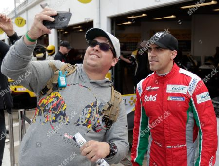 Stock Photo of Pastor Maldonado, of Venezuela, right, takes a selfie photo with a fan after a practice session for the IMSA 24 hour race at Daytona International Speedway, in Daytona Beach, Fla