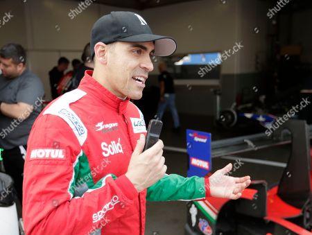 Pastor Maldonado, of Venezuela, stands near his garage after a practice session for the IMSA 24 hour race at Daytona International Speedway, in Daytona Beach, Fla