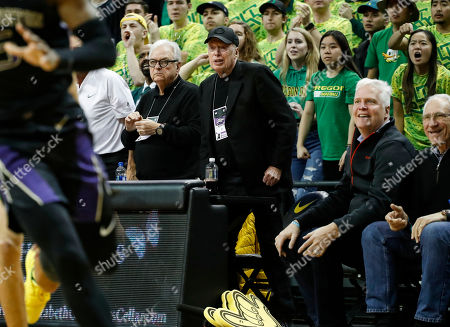 Nike co-founder Phil Knight, at center with dark cap, reacts as Oregon comes back against Washington during an NCAA college basketball game, in Eugene, Ore