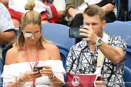Australian cricketer David Warner (R) and partner Candice Warner (L) attend the men's singles semi final match between Novak Djokovic of Serbia and Lucas Pouille of France at the Australian Open Grand Slam tennis tournament in Melbourne, Australia, 25 January 2019.